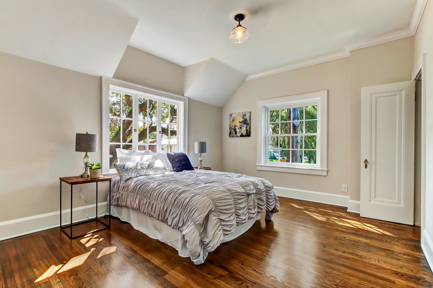 Spacious guestroom with hardwood floors and natural light