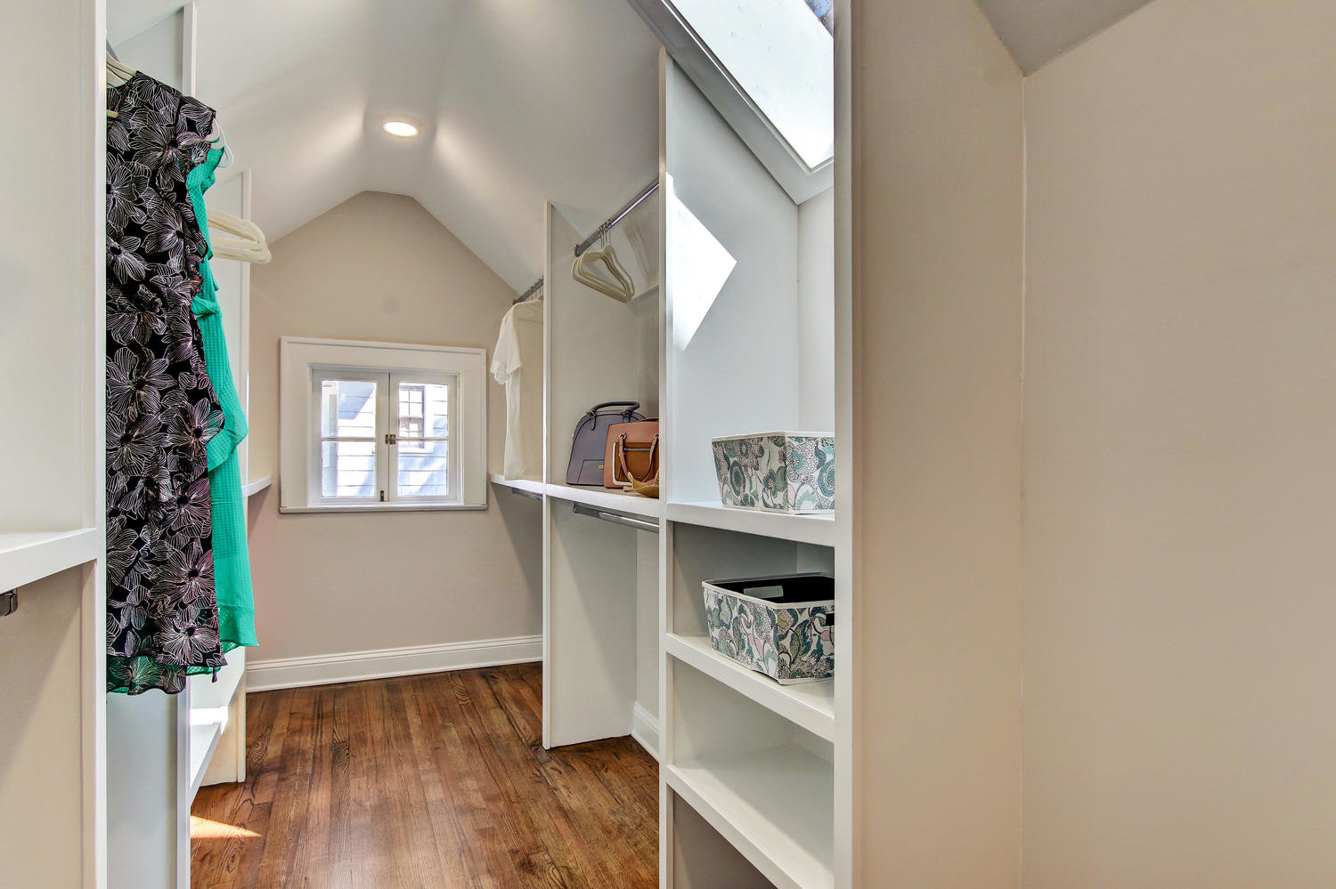 Large walk-in closet  with shelves and skylight